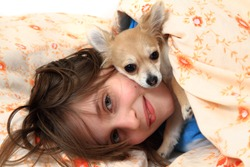 small girl and her chihuahua in the bed