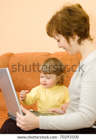 Small girl and mother with laptop at home
