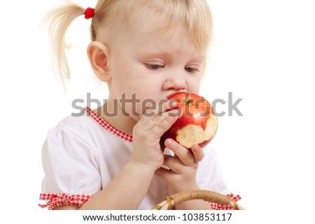 small girl biting an apple