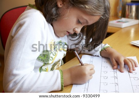 Small Girl doing her homework - stock photo
