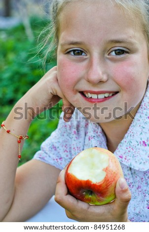 Small girl eating apples