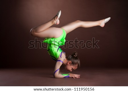 small girl gymnast stand on hands