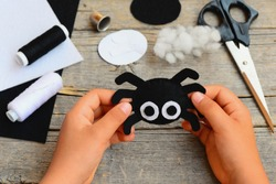 Small girl holds a felt spider ornament in his hand. Girl made a Halloween felt spider crafts. Easy felt crafts for beginners. Halloween sewing craft kit