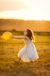 small girl in grey dress runs for with a balloon on a sloping a wheat field in the village at sunset