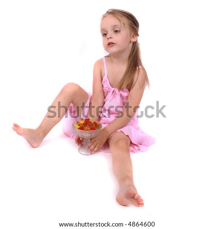 Small girl in pink dress sitting on the floor  and  eating gummy bears