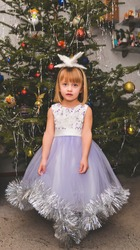 Small girl in snowflake costume near Christmas tree, as costume party for evening celebration. Christmas concert of portrait girl near tree and waiting for gifts.