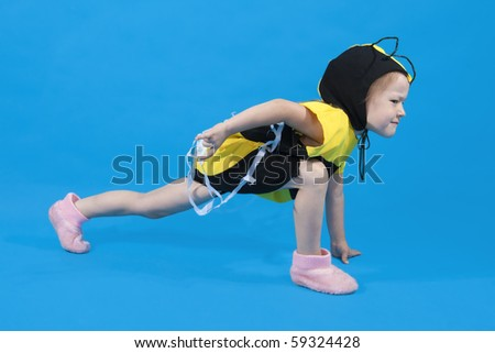 Small girl is dressed at bee costume on blue background