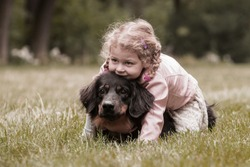 small girl is plying with dog hovawart in the park, vintage