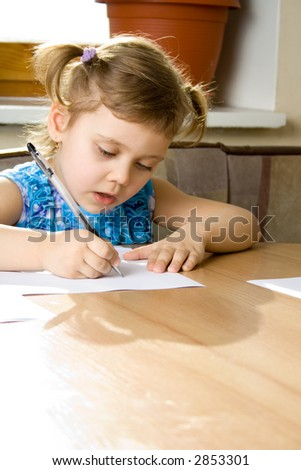 small girl learns to write, seat at a table