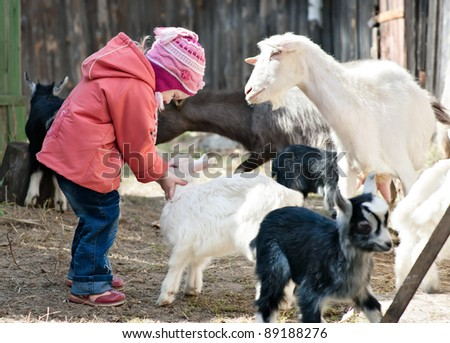 small girl playing with goat