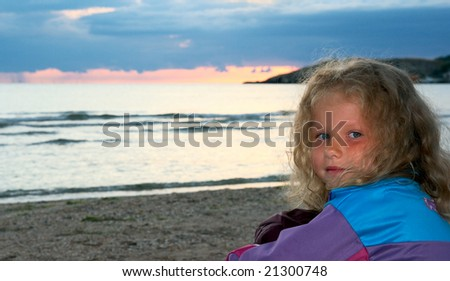 Small girl portrait on evening sandy evening sea coast