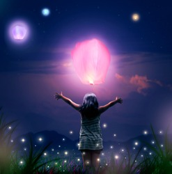Small Girl Releases a Glowing  Sky Lantern Up on a Night Sky. Fantasy Scene and Lantern Festival Concept. Healing, Solitude and Condolences Theme.