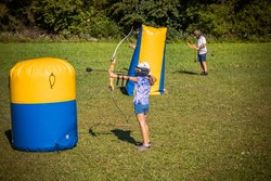 Small girl shooting an arrow from a bow during a game of archery tag