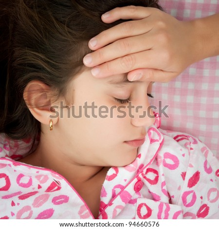 Small girl sick with fever and a woman's hand touching her forehead