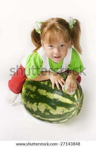Small girl sits on top of the large watermelon