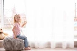 Small girl sitting on ottoman near window