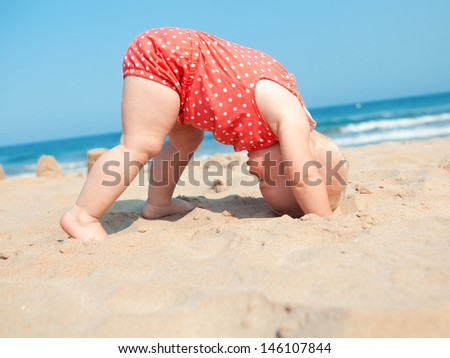 small girl sitting on sand at...