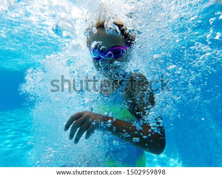 Small girl surrounded by bubbles inside of swimming pool blue waters, wearing watersport goggles and swimsuit enjoy holidays pastime, summer recreation active lifestyle, underwater photography concept #1502959898