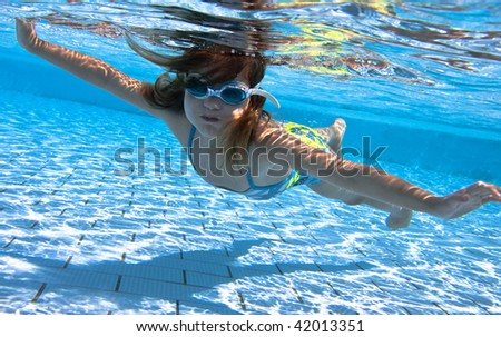small girl swimming under water in the swimming pool