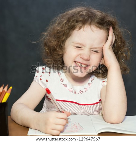 Small girl thought about lessons - stock photo