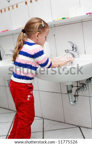 Small girl washing her hands in the bathroom