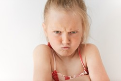 Small girl with blond pony-tail looking seriously, folding hands and frowning eyebrows. Her gloomy appearance says she is very unhappy and offended. Blond baby showing disapproval with pursed lips.