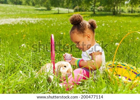 Small girl with Eastern egg and rabbit in park - stock photo