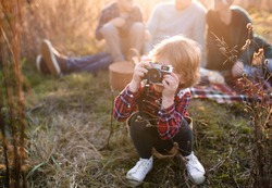 Small girl with family on picnic in autumn nature, taking photographs with camera.