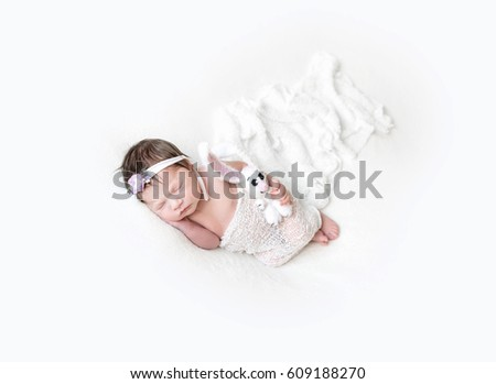 Small girl wrapped with a blanket sleeping with her white bunny with big ears #609188270