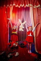 Small girls during a stylized theatrical circus photo shoot in a beautiful red location. Young models posing on stage with curtain. Twin sisters or female friends together