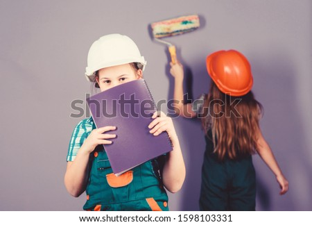 small girls repairing together in workshop. Foreman inspector. Repair. Labor day. 1 may. engineering idea. Future career. Little kids in helmet with tablet and roller. What seems to be a problem