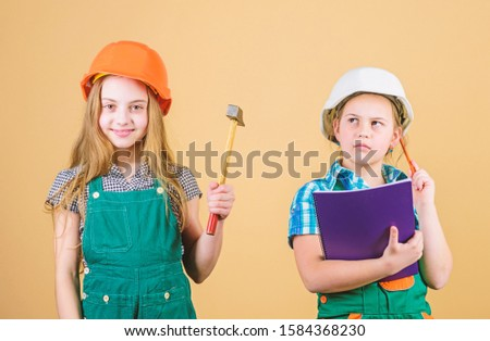 small girls repairing together in workshop. Foreman inspector. Repair. Labor day. 1 may. happy children. Future career. Little kids in helmet with tablet and hammer. Real professional.