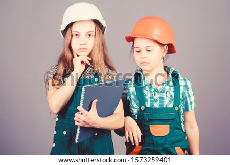 small girls repairing together in workshop. Foreman inspector. Repair. Little kids in helmet with tablet and roller. Labor day. 1 may. engineering idea. house trouble. contractor.