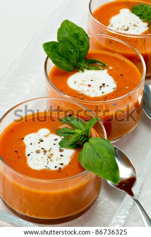 Small glass bowls filled with tomato soup along side sliver spoons.