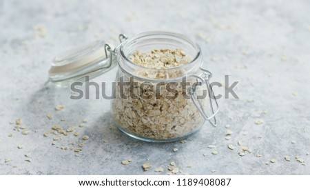 Small glass jar full of oats composed on marble surface of table in daylight