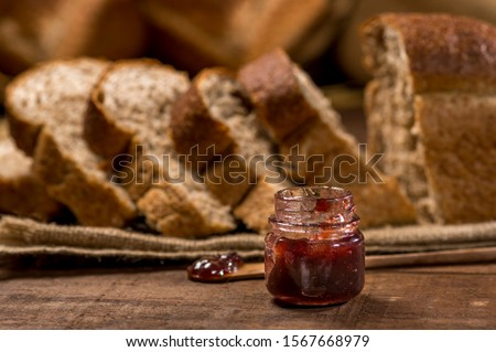 small glass jar with jam, sliced loaf bread made with sesame seeds, sunflower seeds,  linsced, oatmeal, barley, rye, chia, pumpkin seed, poppy, nutmeg, with other breads and ingredients in background