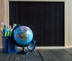small globe, clock and stationery on the wooden table in front of chalkboard. study concept