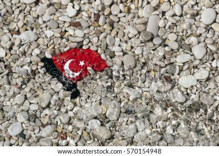 Small glossy ceramic Turkish flag lying in the gravel under water #570154948