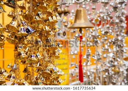 Small golden bells hanging in the Thai temple to pray  for the blessings of Buddhists.