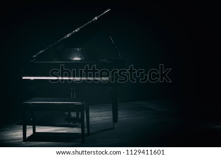 small grand piano in dark room vintage style #1129411601