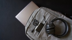 Small gray textile city backpack with laptop or ultrabook, power bank and wireless headphones. Traveling with gadgets. Close-up