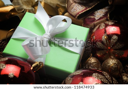 small green box tied with a white ribbon and christmas decoration
