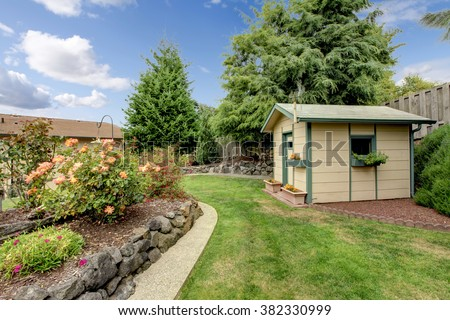 Small green fenced back yard with garden and shed.