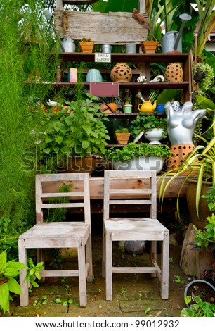 small green garden with many decorations and two wooden chairs - home exterior