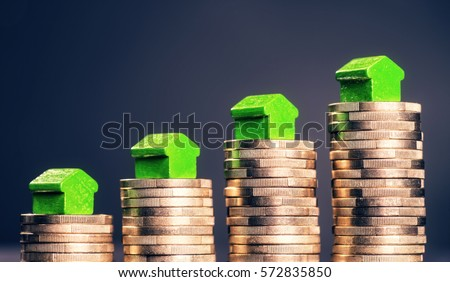 Small green houses standing on stacks of coins.