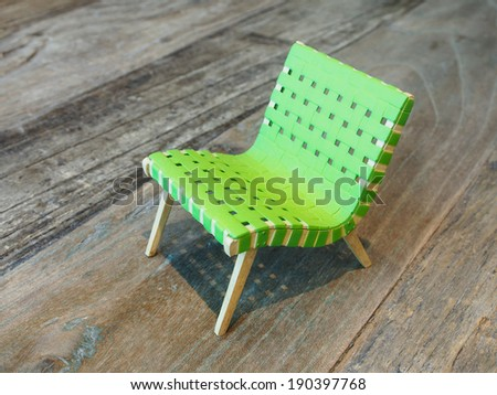 small green relaxing chair on wood background