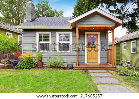 Small grey house with wooden deck. Front yard with flower bed and lawn