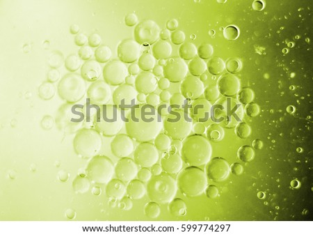Small group, aggregation or collection of half illuminated slightly blurred perfect round spheres of immiscible liquid of varying sizes olive green color #599774297