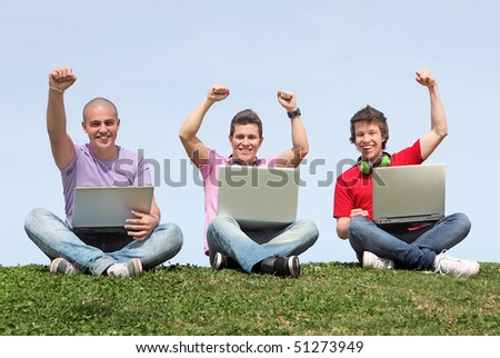 small group of boys or men with laptops and cheering happy.
