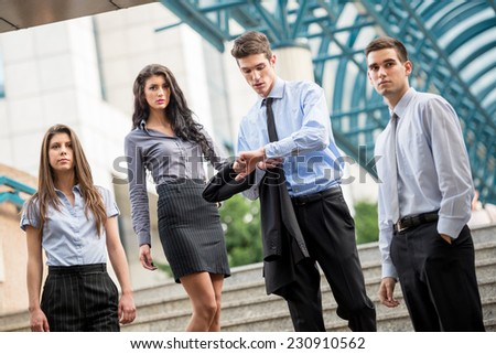 Small group of business people, formally dressed, standing on the steps of the office building as if expecting someone, while a young businessman looking at his watch in his hand. Foto stock ©